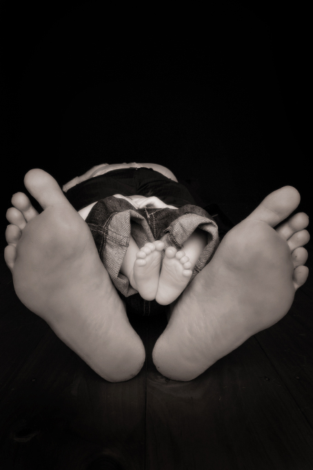 Black and white studio picture of dads and babies bare feet nestled together