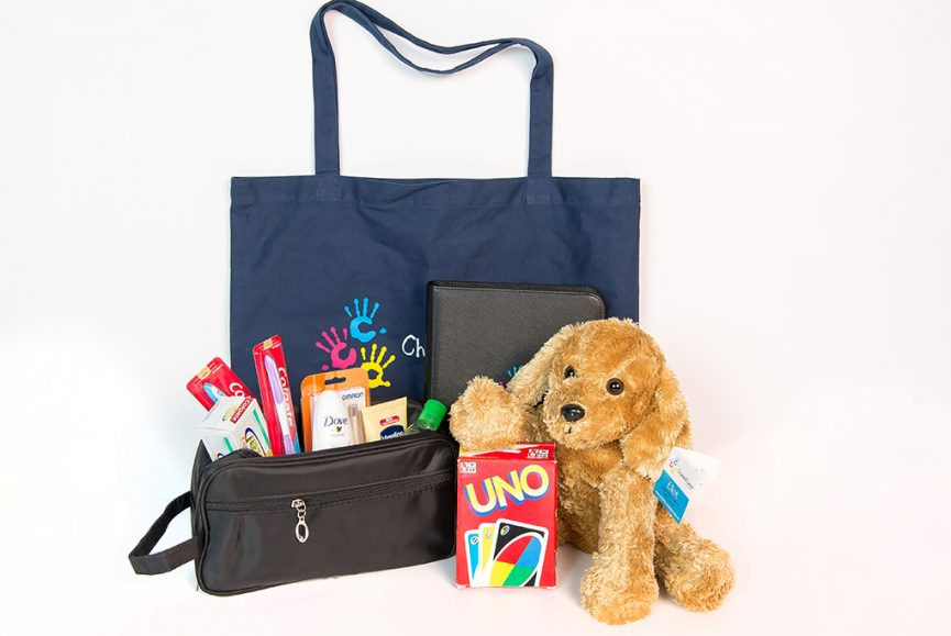 Location shoot using portable studio, image of Eliott the Childhood Cancer Assoi actions  toy mascot dog, image of handout pack give to new clients