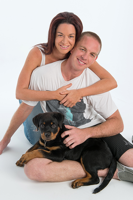 Casual portrait of couple waering tshirts and shorts and denim jeans and their dog on a white background