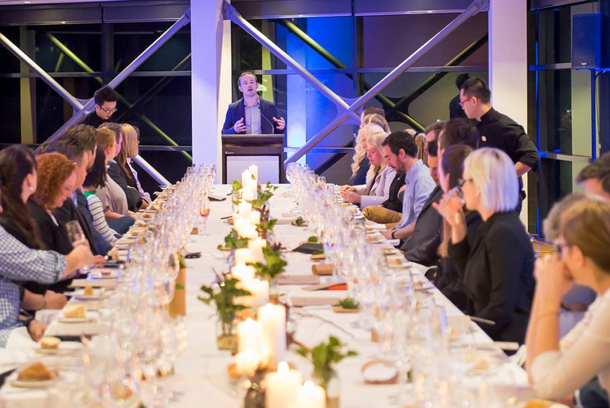Corporate presentation dinner evening image, dinner with speaker at a lecturn, long table dinner with candles, glassware degaustation food menu, National Wine Centre