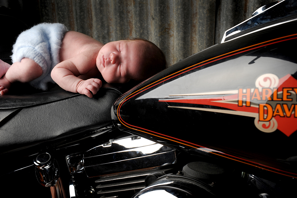 Colour Studio shot against old and rusty galvanised backdrop of little boy sleeping on harley davidson motorbike dreaming of his own future motor bike adventure