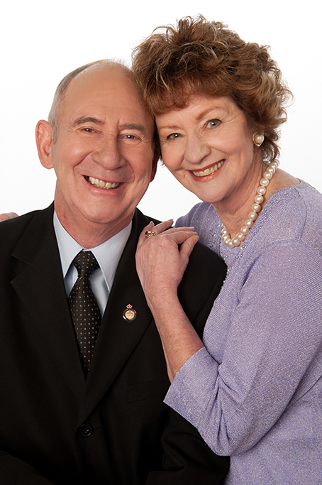 mature couple in formal clothing of suit and tie dress with pearls in studio on modern white background