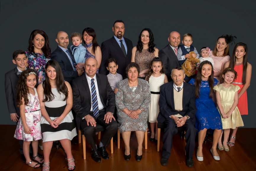 italian family generations studio portrait session with 21 family members, comprising grandparents, parents, children and grandchildren as classic formal studio portrait group in colour with formal clothing