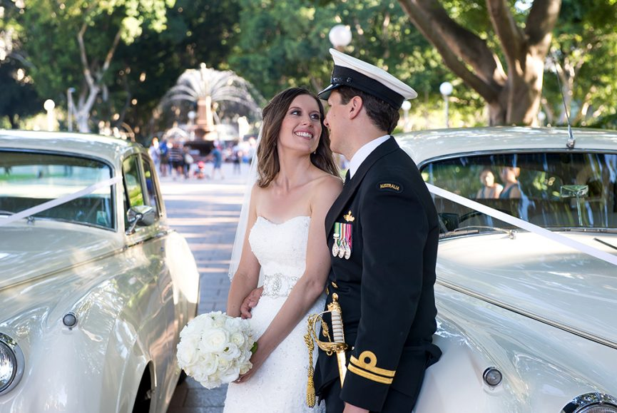 Water fountain, feature, Hyde Park, Australia, light posts, trees, Sydney, gardens, wedding, cars, bride, happy, love, groom, dress, lace flowers, embellished, roses, bouquet, photography, stripes, black, sword, badges, gold, medals, officer, hat, navy, uniform, military, smile, beautiful, candid, moments, photographer