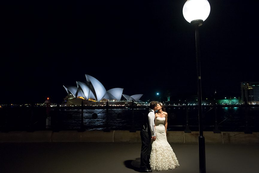 beautiful, bride, groom, Sydney, Opera House, water, dress, lace, fishtail, wedding, happy, kiss, newlyweds, suit, white shirt, pants, vest, Harbor, Australia, reflection, photography, lights, photographer