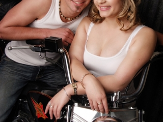 casual shot of young couple wearing white singlets and denim jeans with harley davidson heritage soft tail