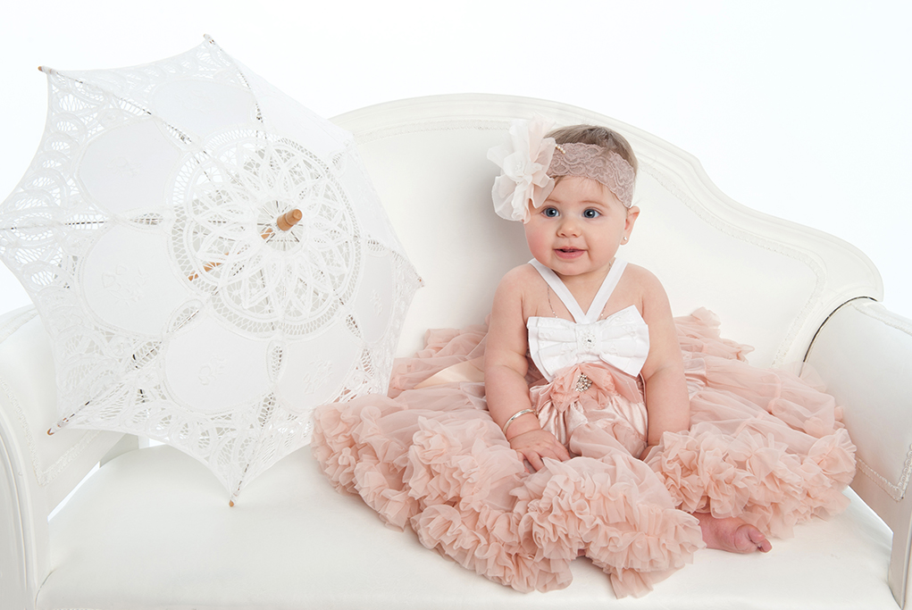 White modern studio shot of cute little girl in soft pink party dress wihg large whot bow and lace headband with large flower rosette sitting on with leather love seat with vintage white lace umbrella